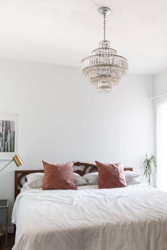 une chambre bohème moderne dans des tons neutres et pastels avec un lustre en cristal vintage sur le lit