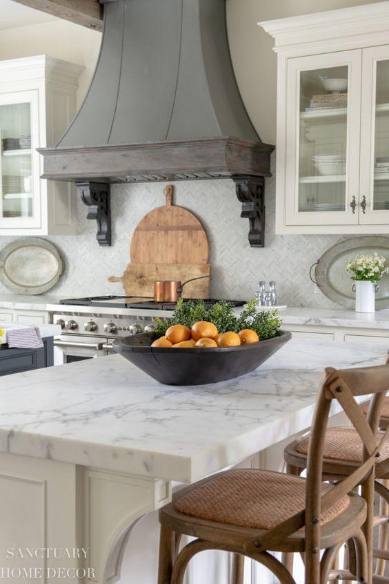 une cuisine neutre avec des comptoirs en pierre blanche et une hotte en métal vintage en gris pour ajouter du chic et de la couleur