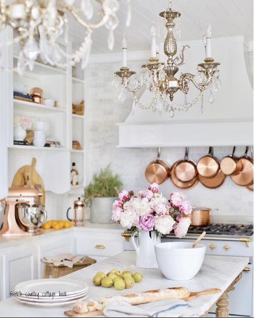une cuisine blanche moderne et élégante avec deux lustres vintage qui ajoutent chic et beauté à l'espace