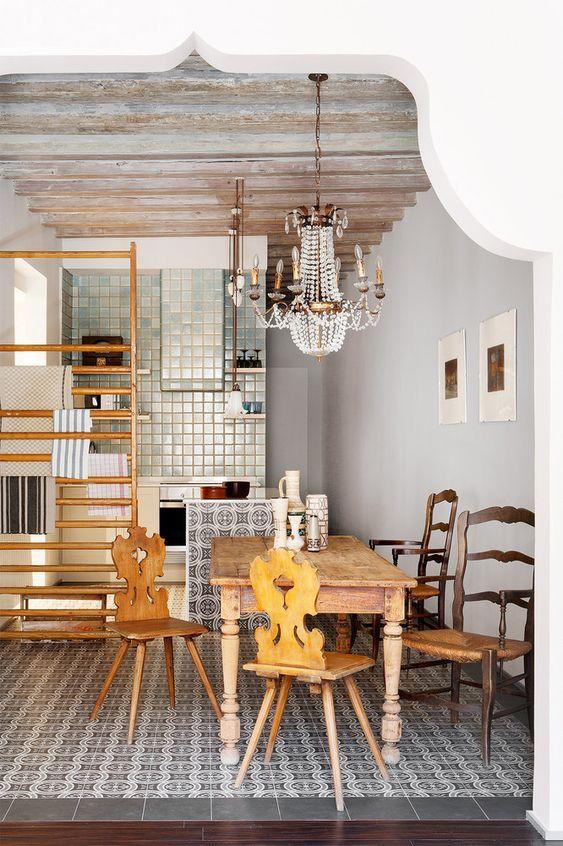 un espace éclectique avec des carreaux imprimés, un ensemble de salle à manger en bois et un magnifique lustre vintage en cristal au-dessus de l'espace