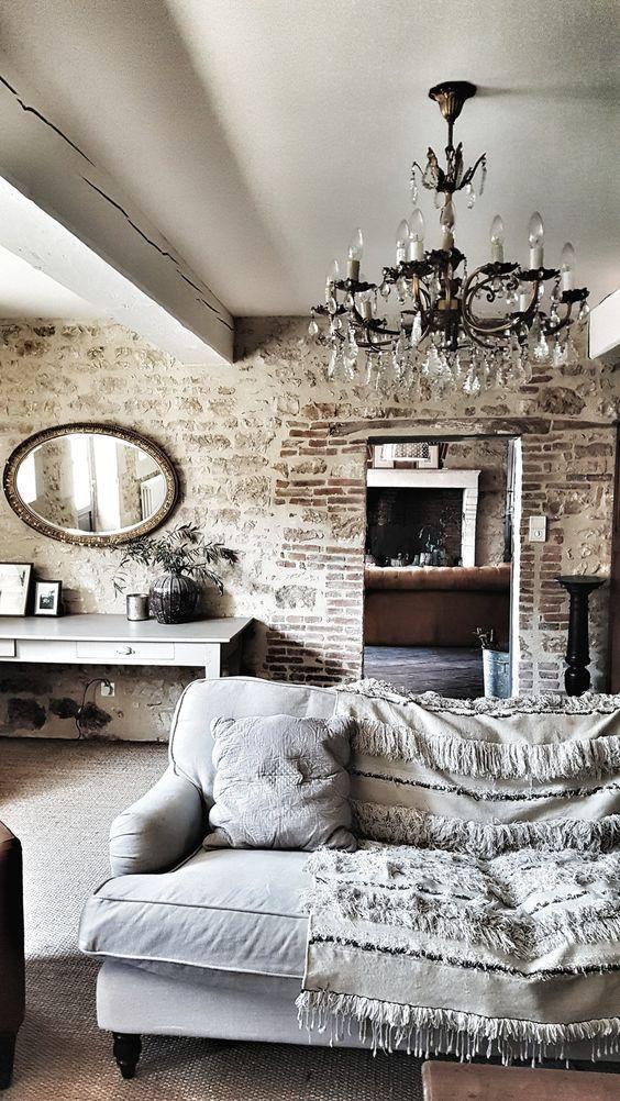un espace industriel rencontre contemporain adouci avec un miroir vintage et un lustre pour un look raffiné