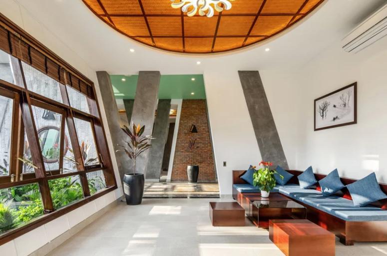 Le salon est minimaliste mais décoré dans des couleurs vives, avec de riches meubles et cadres de fenêtres en bois teinté ainsi qu'un rembourrage bleu