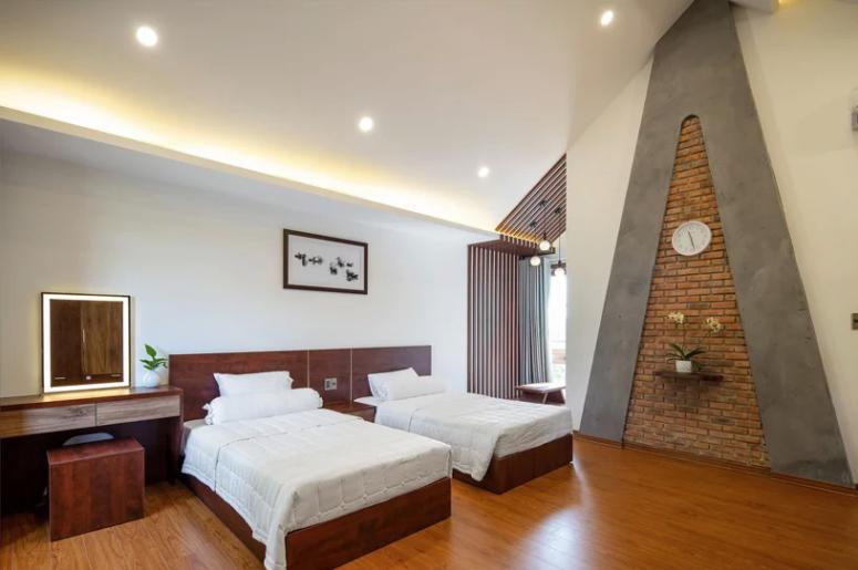 La chambre d'amis est composée de deux lits, d'un coin coiffeuse, d'une grande fenêtre et d'une décoration murale fraîche