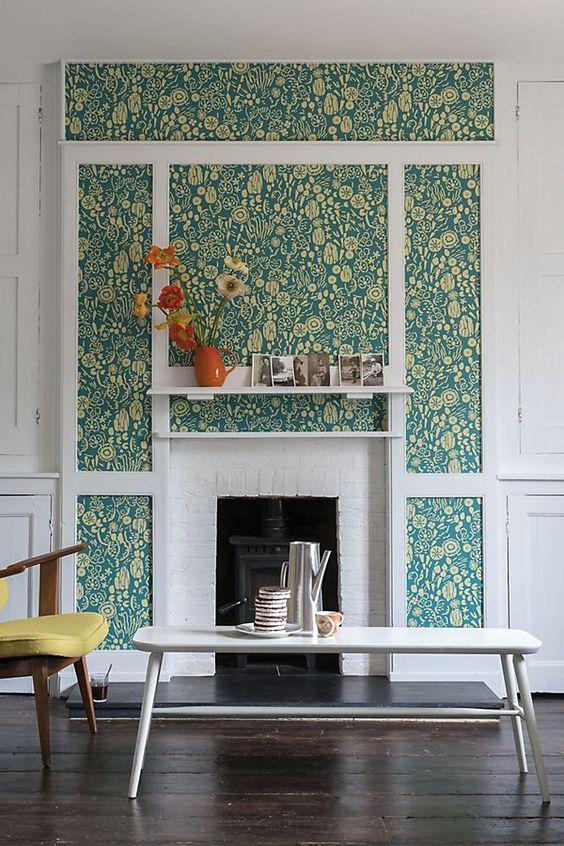 un salon neutre avec un papier peint à motifs botaniques d'inspiration rétro qui ajoute de la couleur et des motifs à l'espace