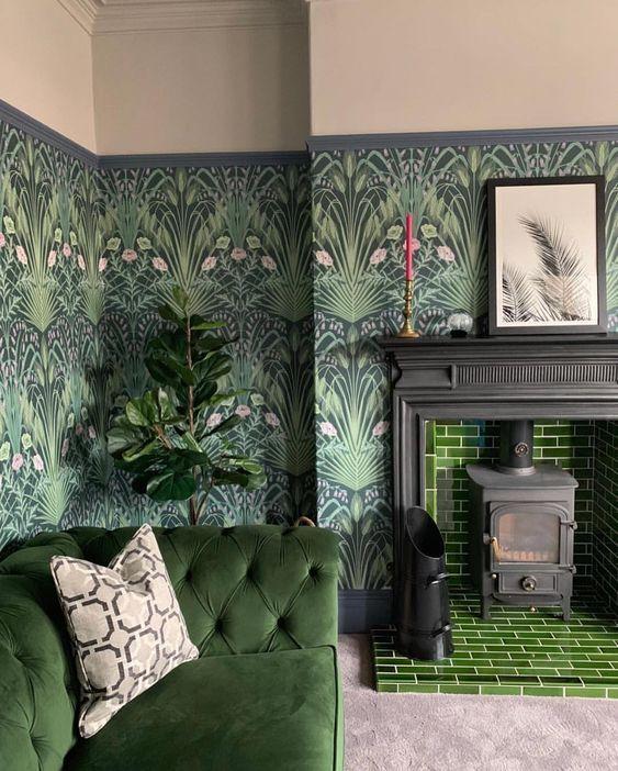 un salon de mauvaise humeur avec un papier peint botanique sombre, des carreaux verts, un canapé assorti et des plantes en pot se sent à l'extérieur