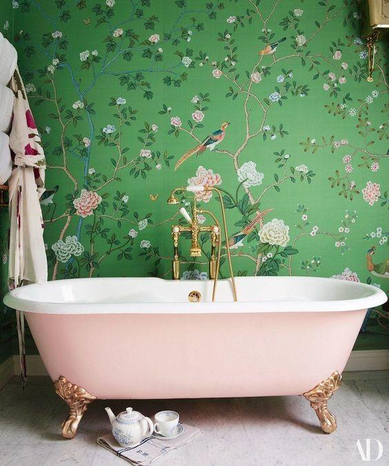 une salle de bain chic pour filles avec du papier peint sur la flore et la faune, une baignoire sur pattes rose et des accessoires dorés est incroyable