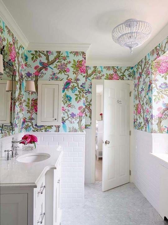 une salle de bain entièrement neutre avec un papier peint flore et faune super lumineux pour ajouter une touche de couleur à l'espace