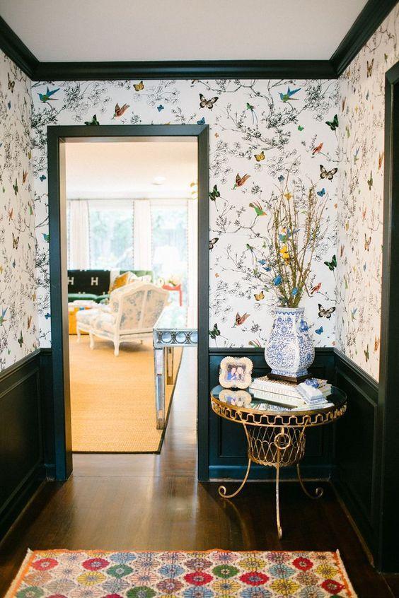 une entrée fantaisiste avec du papier peint de la flore et de la faune aux couleurs vives, des meubles chics et raffinés et un tapis