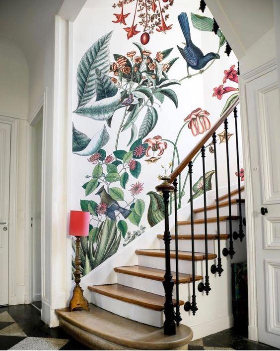 une entrée raffinée avec un escalier classique et un fantastique papier peint floral et faune lumineux plus un petit lampadaire en rouge