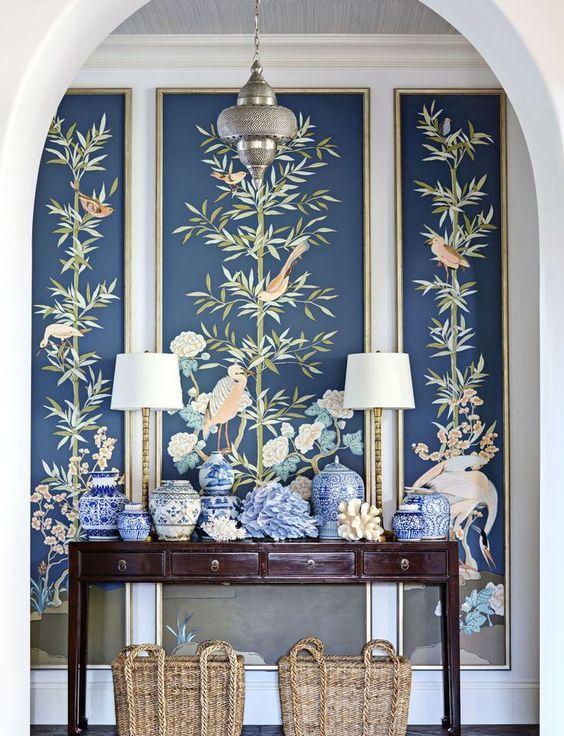 une entrée avec une console, des vases bleus, des lampes et un papier peint de faune et de flore sombre pour une déclaration