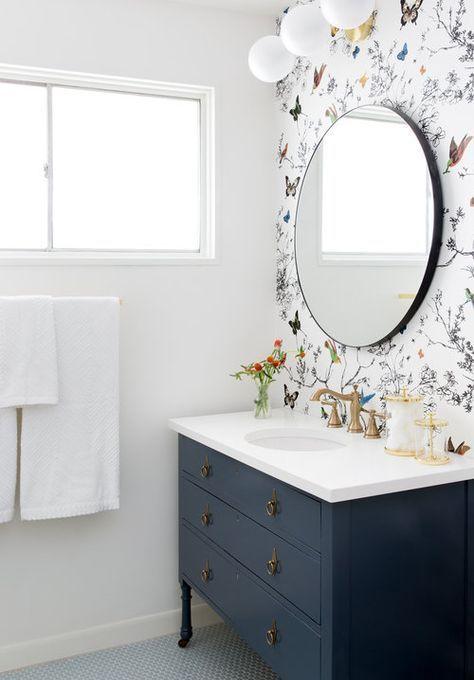 une salle de bain neutre avec une vanité noire, un papier peint floral et animalier et un miroir rond pour un look audacieux