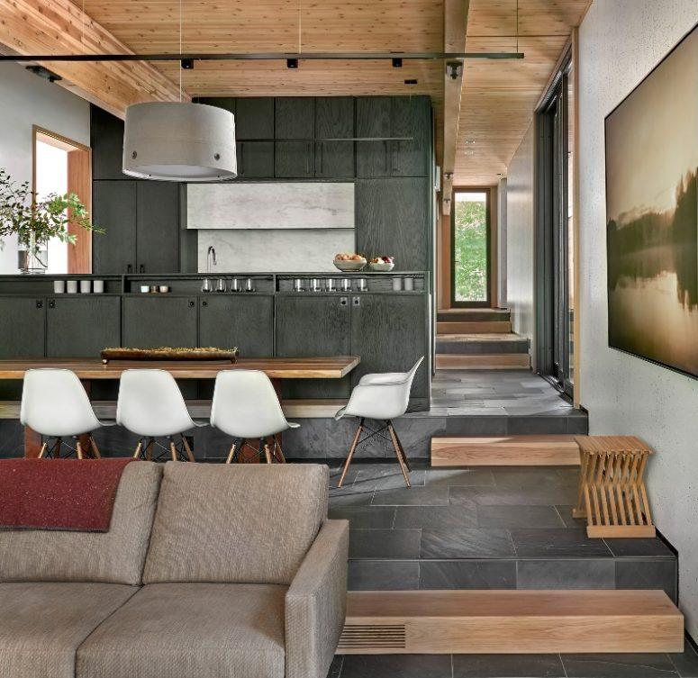 La maison est une mise en page ouverte avec un salon et une zone à manger et une cuisine ensemble, il y a beaucoup de bois et de contreplaqué dans la décoration
