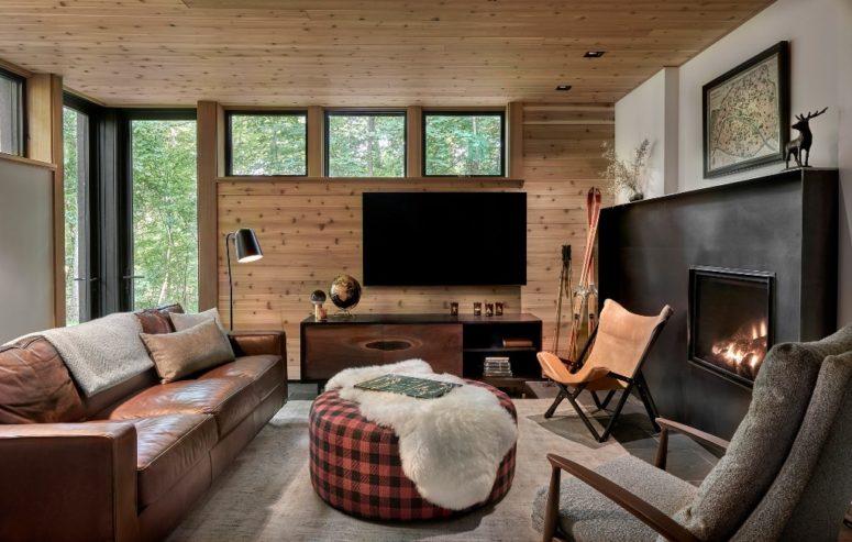 L'espace est fait avec un canapé en cuir, une cheminée, des vitrages et du bois naturel recouvrant les murs