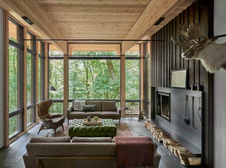 Un autre salon est fait avec des meubles élégants neutres, une cheminée et un vitrage complet pour profiter de la vue