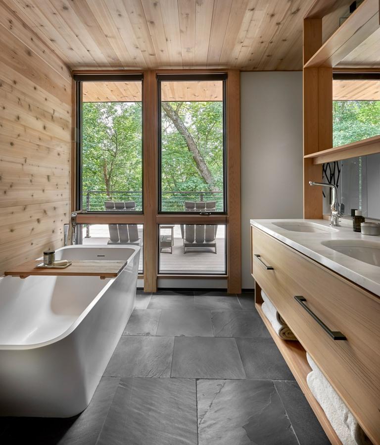 La salle de bain est faite avec des carreaux sombres, beaucoup de bois, une double vasque et une baignoire sculpturale