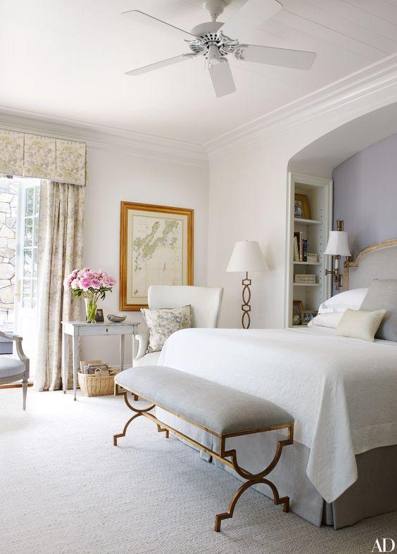 une chambre vintage faite dans tous les tons neutres, avec un banc chic sur pieds en laiton et un lampadaire assorti dans le coin