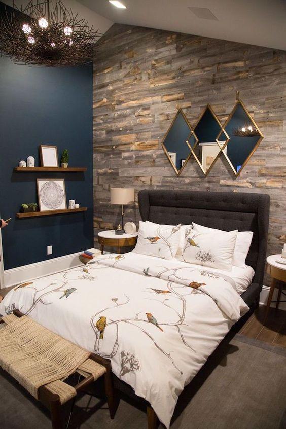 une chambre luxueuse avec un mur d'accent bleu marine, un bois récupéré et un magnifique miroir géométrique métallique