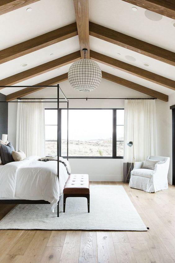 une chambre de ferme neutre avec des poutres en bois au plafond et une lampe sphère