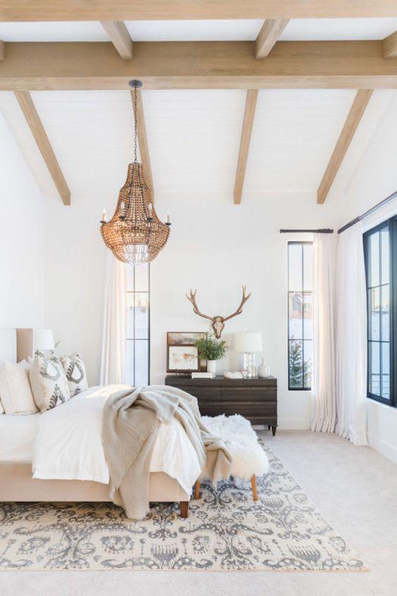 une chambre éclectique neutre avec des poutres en bois au plafond, un lustre en laiton avec des bougies