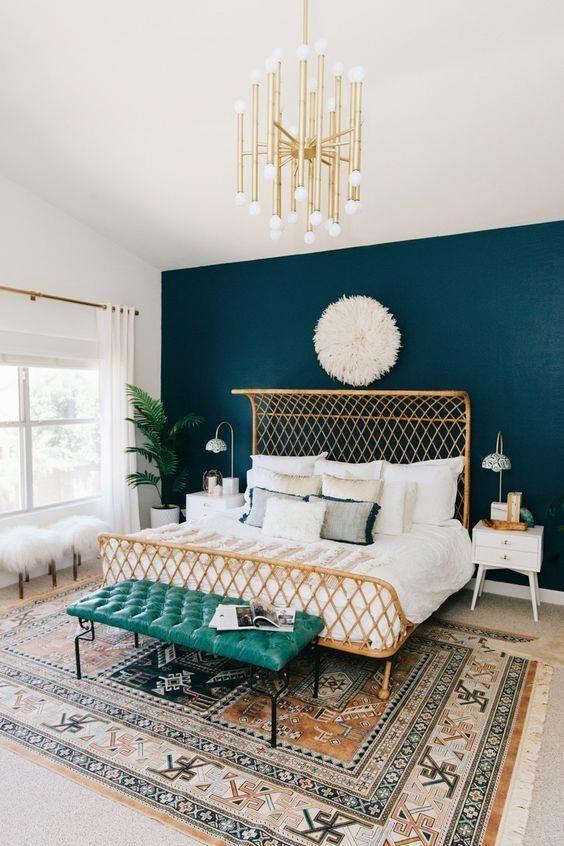 une chambre chic agrémentée d'une plante en pot, d'un lustre en or et d'un agencement de plaids