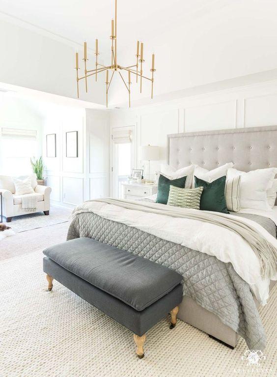 une chambre neutre avec un lit de déclaration gris, un arrangement d'oreillers