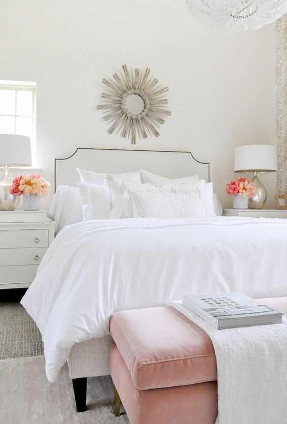 une chambre chic et aérée avec un lit blanc et un agencement d'oreillers blancs mais de tissus variés