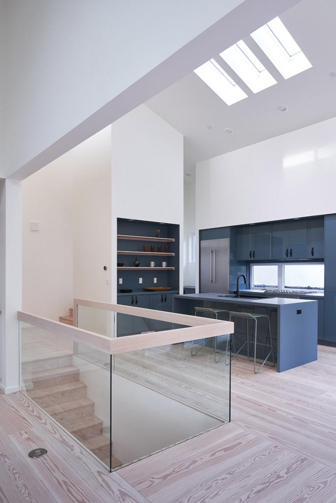 La cuisine est faite de manière minimale, avec des armoires grises, avec des étagères intégrées et une balustrade en verre