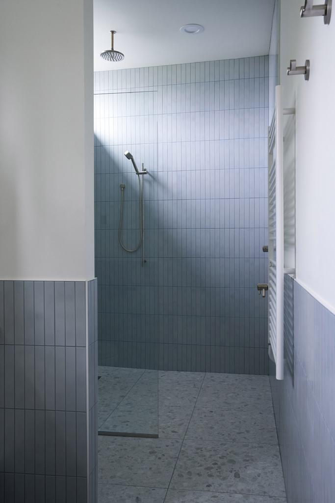 La salle de bain est grise et blanche, avec des carreaux longs et fins et un sol en terrazzo