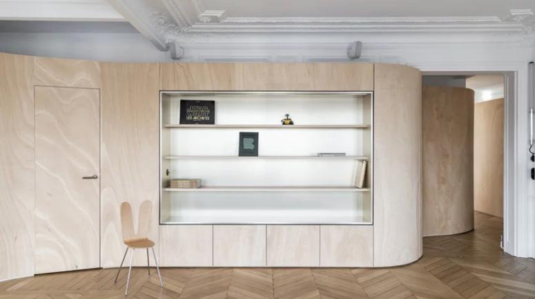 Ce mur en bois dispose également d'un espace de rangement et enveloppe tout l'appartement en le divisant en zones et en gardant les touches historiques visibles