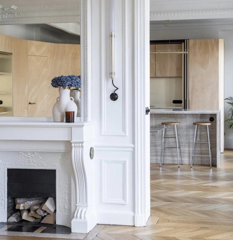La cuisine est neutre, avec des armoires en contreplaqué clair, il y a un îlot de cuisine en pierre