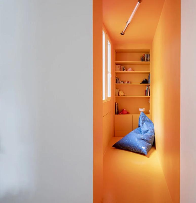 Il y a un coin lecture pour enfants avec des murs en contreplaqué lumineux et des étagères intégrées