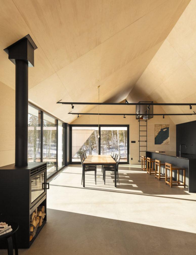L'espace décloisonné comprend également une salle à manger et une cuisine, un îlot de cuisine noir et des chaises noires