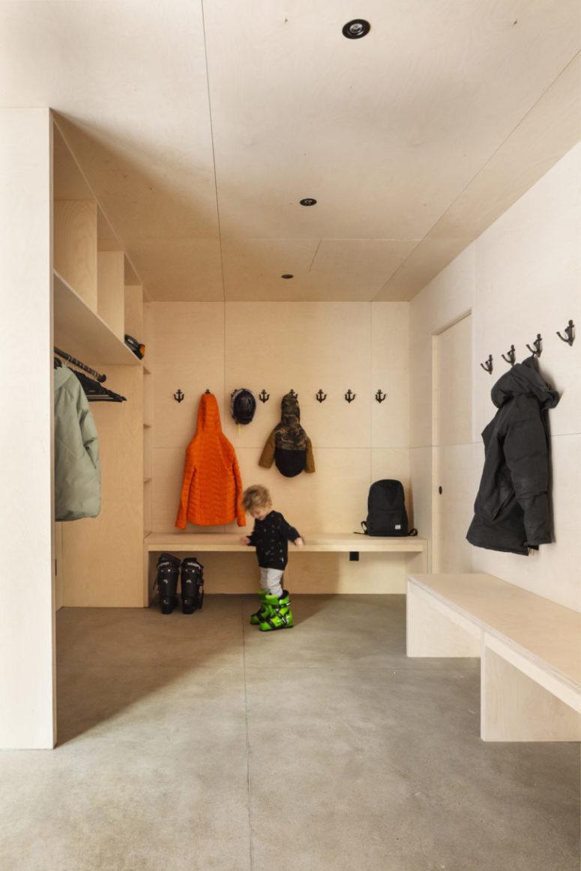 Le vestiaire est revêtu de contreplaqué de couleur claire, tous les meubles sont faits du même contreplaqué