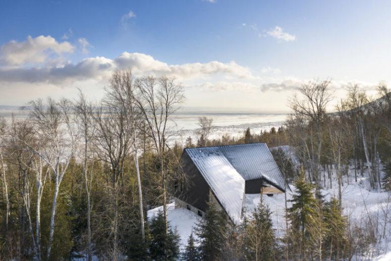 Voici à quoi ressemble la maison de l'extérieur, avec une vue sur les bois et un lac à proximité
