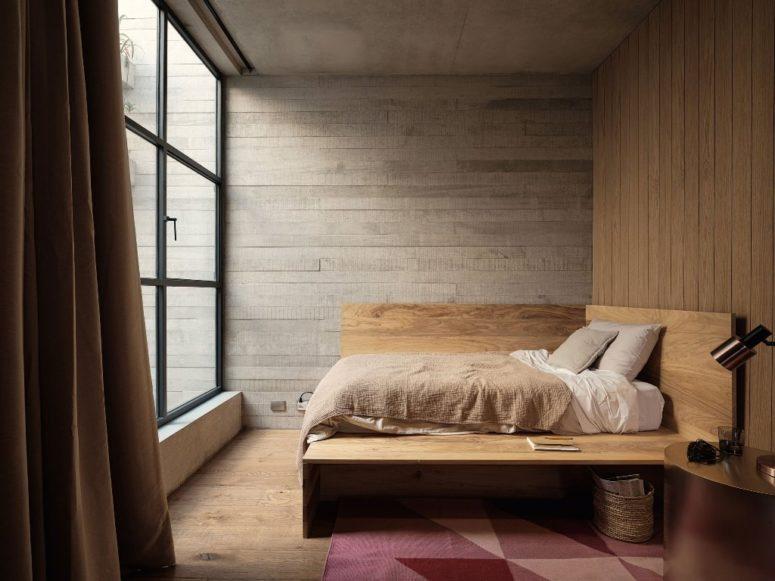 Cette petite chambre comprend un lit original, un tapis audacieux, un panier et une table de chevet en métal poli