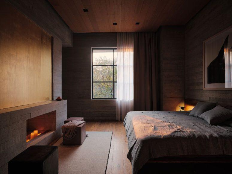 Cette chambre comprend beaucoup de bois, un grand lit et une fenêtre, une cheminée non fonctionnelle avec des bougies