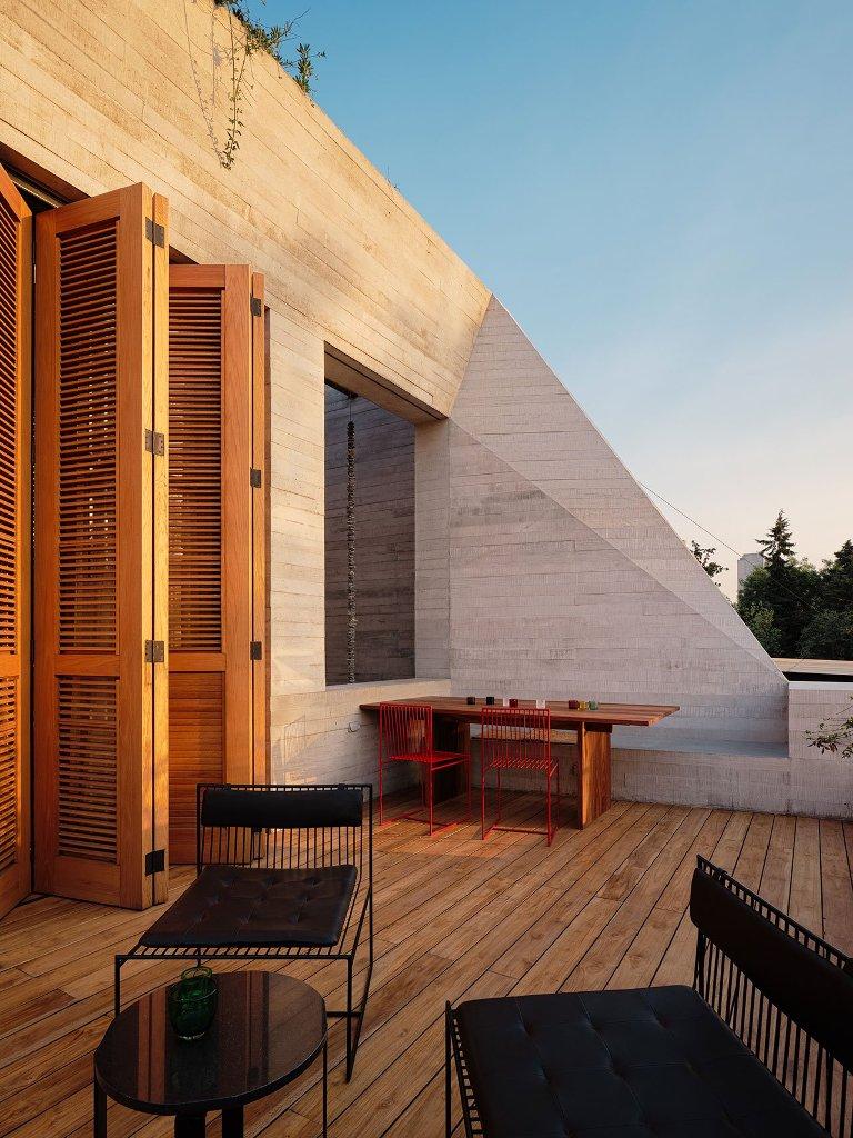 Il y a une terrasse avec des portes à volet et un mobilier moderne simple en rouge et noir