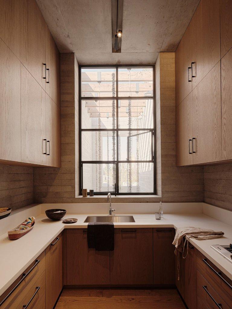 La cuisine est faite avec des armoires neutres, des comptoirs en pierre blanche et une grande fenêtre