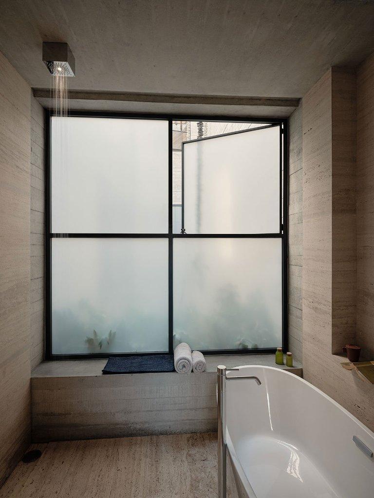 La salle de bain est dotée d'une fenêtre en verre dépoli, d'une baignoire ovale et d'articles simples mais luxueux