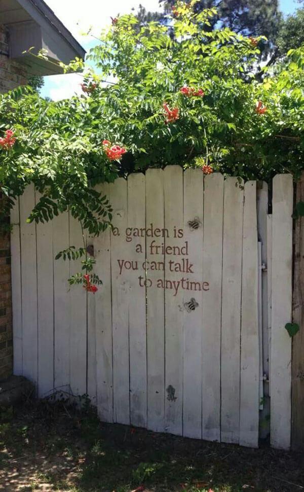 Message au pochoir sur une porte de jardin blanchie à la chaux