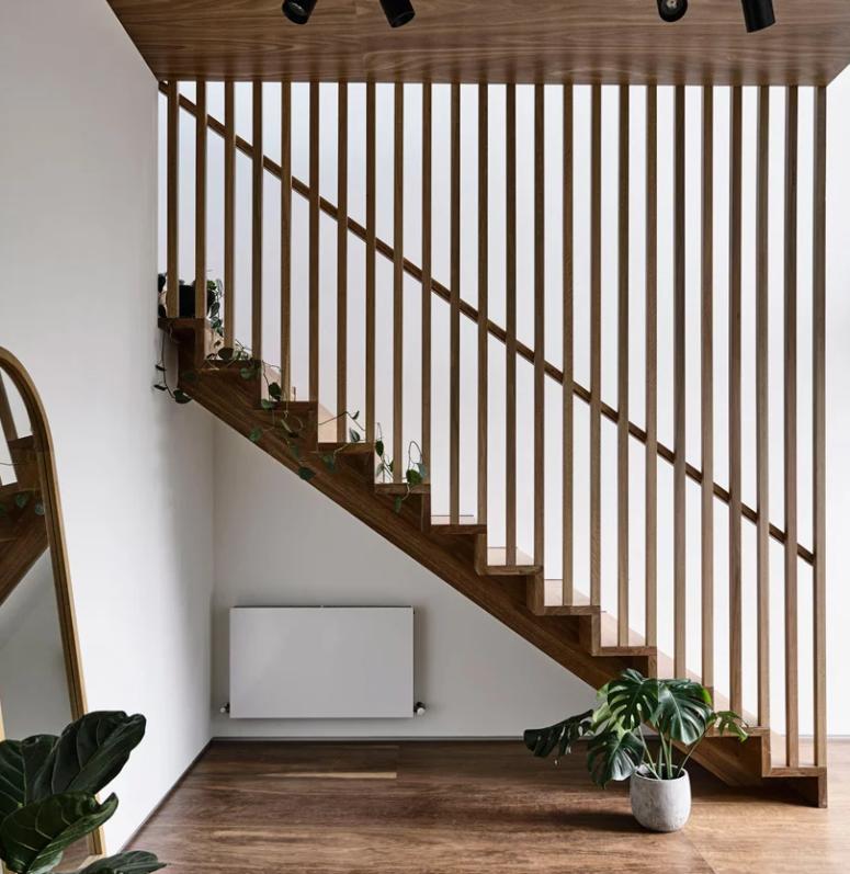 L'escalier est divisé par un écran en planches de bois du reste de l'espace
