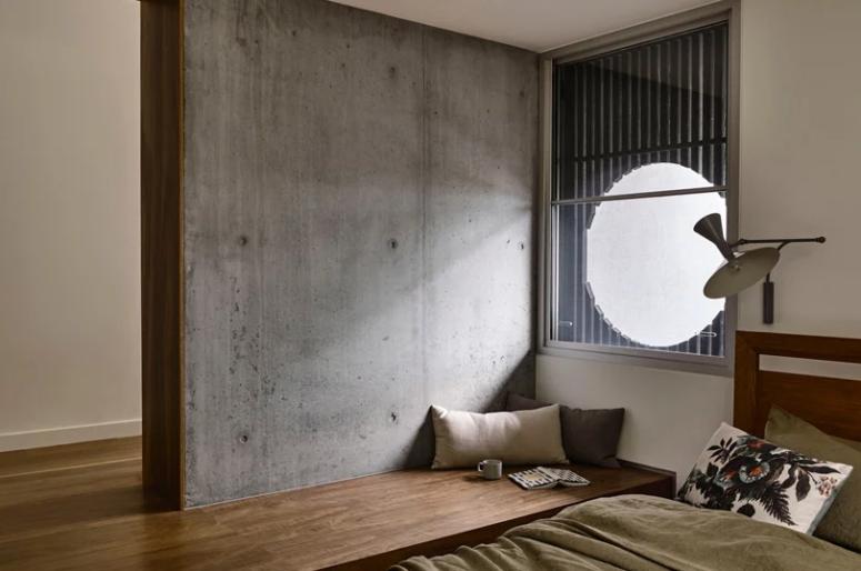 La chambre comprend un lit et une plate-forme qui forme un lit de repos en bois, une fenêtre ronde avec un paravent en bambou
