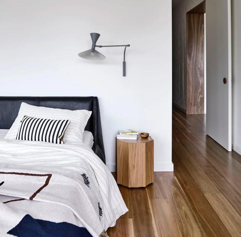 Une autre chambre est remplie de lumière, il y a un lit et des appliques en cuir noir ainsi que du bois et du contreplaqué