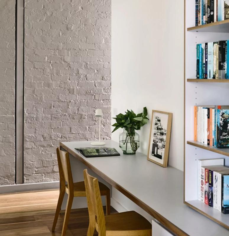 Le bureau à domicile est fait avec un mur de briques blanches, un bureau avec doublure en bois et une unité de rangement sur le dessus