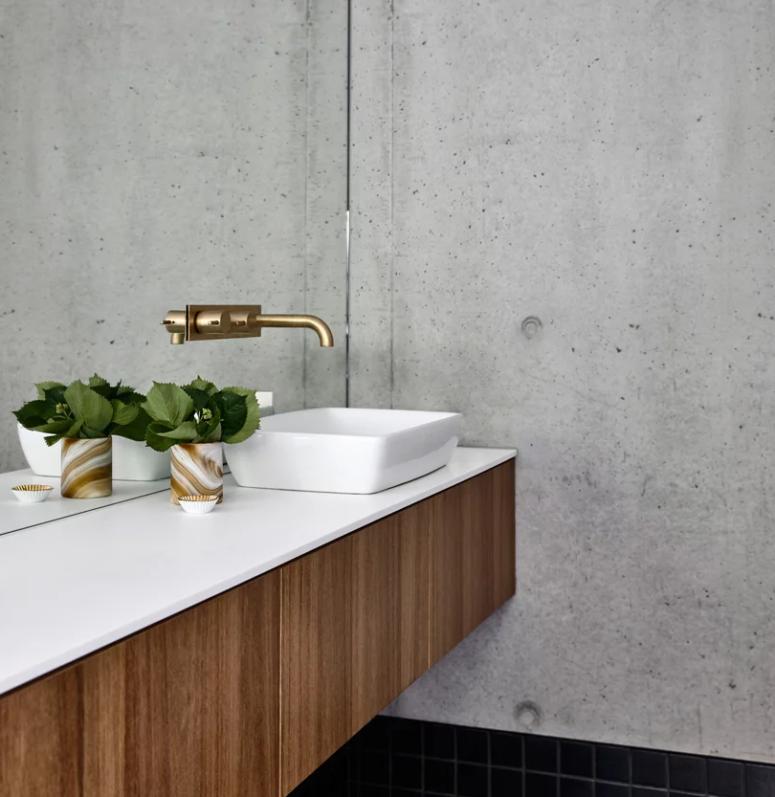 La salle de bain est faite avec du béton et des carreaux noirs, une vanité murale et un lavabo carré