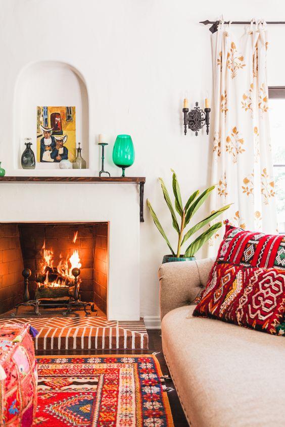 un espace espagnol moderne et lumineux avec des textiles imprimés colorés, des touches lumineuses, des murs blancs et une cheminée, des plantes en pot