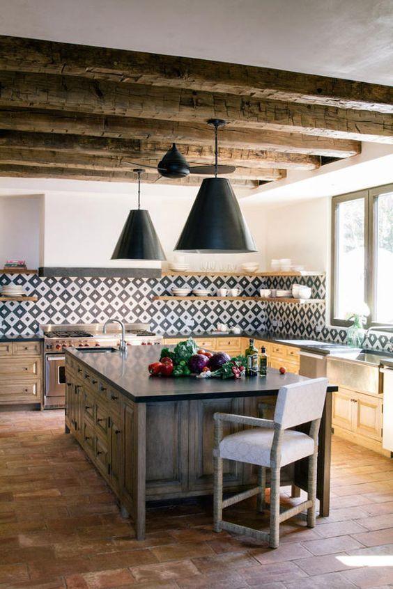 une cuisine espagnole moderne et lumineuse avec des poutres en bois, un dosseret de carreaux imprimés, des suspensions et un îlot de cuisine en bois épais