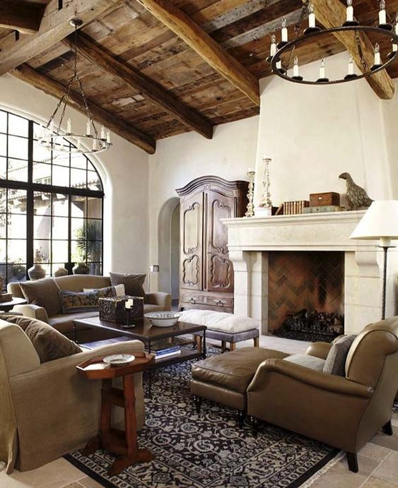 un salon espagnol chic avec des murs en plâtre blanc, un plafond en bois récupéré avec des poutres, des meubles neutres et des lustres vintage