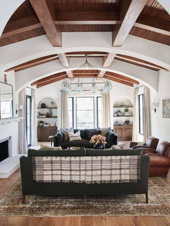 un salon espagnol chic avec des murs et des plafonds blancs, des poutres en bois, des meubles sombres et un lustre accrocheur