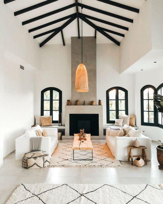 un contemporain rencontre un salon espagnol traditionnel avec une cheminée en béton, des meubles neutres et des textiles imprimés